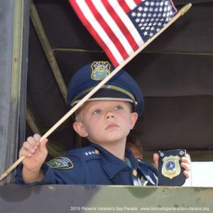 Child Waving American Flag inside Parade Vehicle