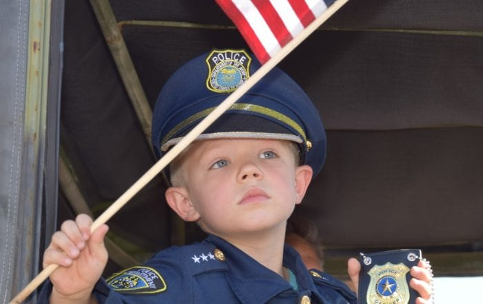 Child Waving American Flag inside Parade Vehicle