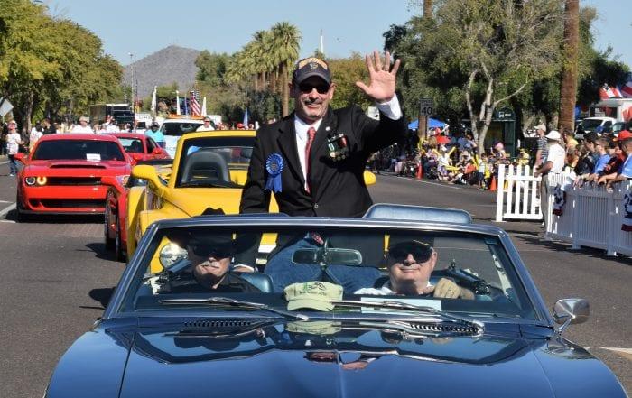Chris Oshana rides in vehicle during Phoenix Veterans Day Parade